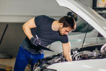 Mechanic examining under hood car and writing notes at repair garage