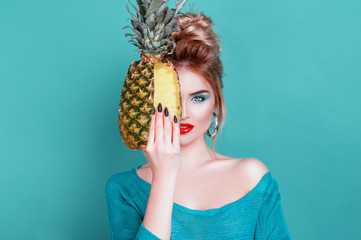Tasty tropical fruits! Attractive sexual woman with beautiful makeup holding fresh juicy pineapple and looking at cam on isolated blue background. Summer Fashion Lifestyle Creative Healthy Food