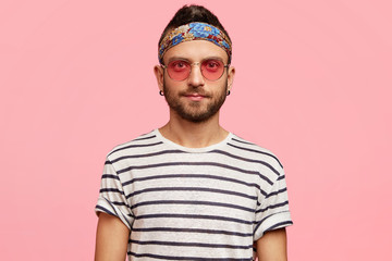 Horizontal portrait of serious bearded young male hippie in stylish sunglasses, headband and striped t shirt, poses against pink background, looks confidently into camera. Hippy guy with stubble