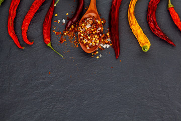 Red and yellow chili pepper dried. On a stone black background.