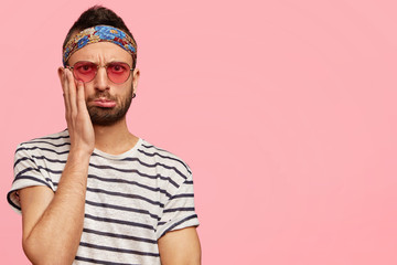 Photo of displeased puzzled male hippie with stubble, keeps hand on cheek and looks in bewilderment at camera, isolated over pink background with copy space for your advertisement or promotion