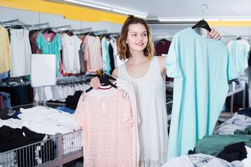 Cheerful girl customer selecting new garments