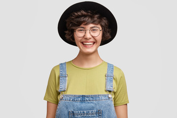 Photo of amazed female geek student being shocked to fail exam, crams all time, can`t believe in failure. Attractive young woman designer in round glasses, black hat feels great surprisement