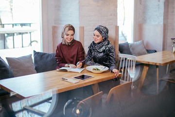 Two young pretty muslim business woman in head scarf write in notebook