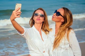 two women do selfie on vacation on the beach
