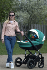 a woman with a baby carriage walks