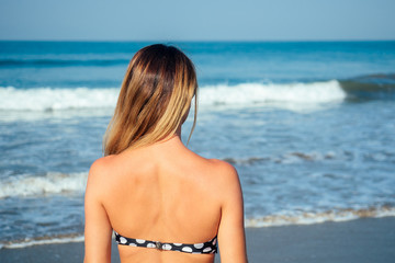 shoulders and back of a woman in a swimsuit on the beach