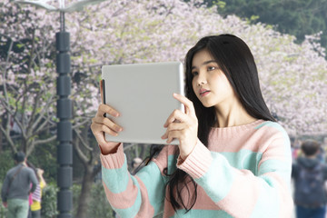 Young girl taking photo of blooming flower with digital tablet.