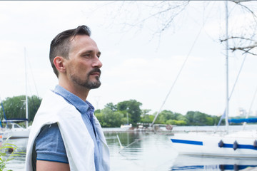 Portrait of young man with yacht. Man profile on the river bank. Man with model cut hair and bearded goatee.