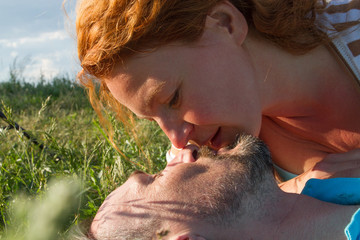 Close up of faces before kiss in green grass. Close up Summer kiss of Man and woman