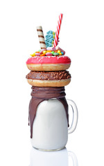 Crazy milk shake with pink and chocolate donuts, color candy and straw in glass jar