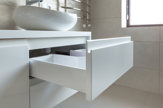 Opened U-shaped drawer in a bathroom furniture, white glossy front, handless design.