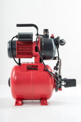 Red surface water pump. White background