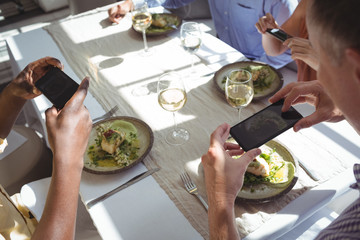 Friends taking picture of food from mobile phone
