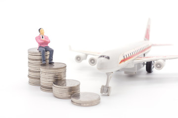 Miniature businessman standing on coins and the airplane behind. saving and loan concept.