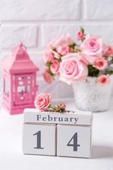 St. Valentine Day background. Calendar, tender pink roses flowers and  pink lantern against  white brick wall.