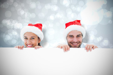 Festive young couple smiling at camera against light glowing dots design pattern