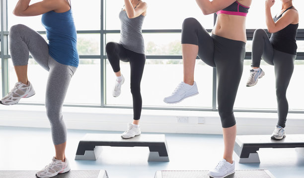 Women raising their legs while doing aerobics