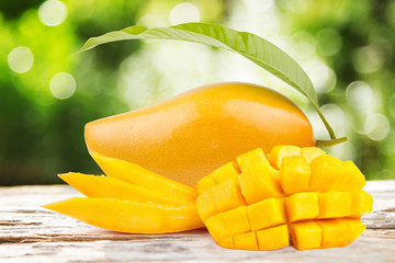 Mango fruits and slice cut with leaf on wood table with green nature background