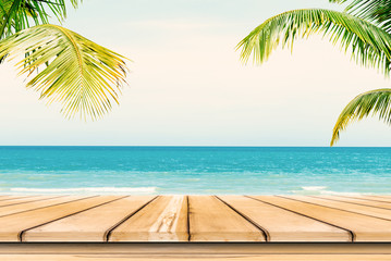 Empty wooden table and palm leaves background in summer time.