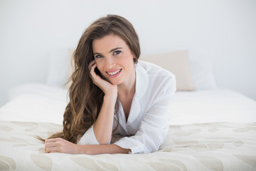 Smiling casual brown haired woman in white pajamas lying on her bed