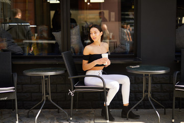 Brunette girl stand on the street look at camera and dring her delicious coffee from white cup, spring time photo shoot
