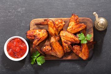 baked chicken wings on wooden board