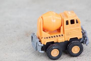 Plastic toy orange color for construction.by Mix cement car on cement floor.