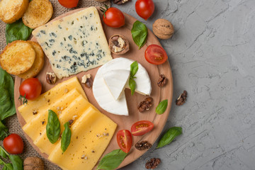 Different kinds of cheeses, with basil, cherry tomatoes, croutons from baguettes. Top view, with empty space for inscription