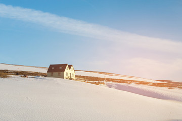 Small cottage over mountain slope with snow covered, Iceland winter season natural landscape background