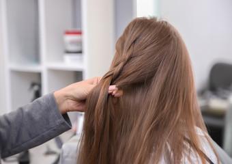 Foto op Aluminium Kapsalon Professional female hairdresser working with little girl in salon