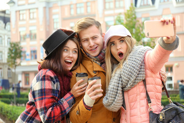 Young happy friends taking selfie outdoors