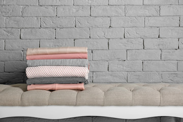 Stack of clean clothes near brick wall indoors