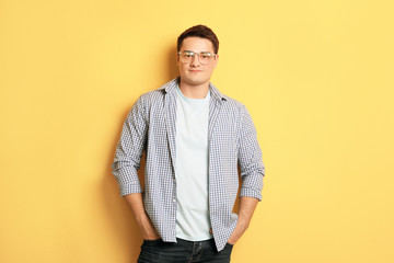 Portrait of confident young man on color background