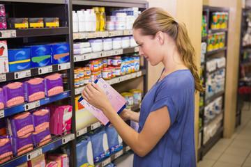 Pretty woman picking box in shelf