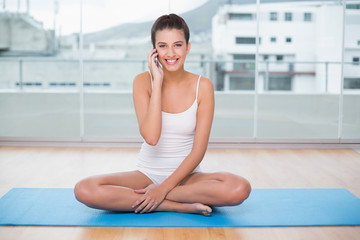 Pretty natural brown haired woman in white sportswear making a phone call