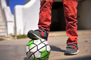 Kid's legs with football