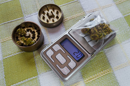 Small digital weighing machine of precision with a plastic bag with two grams of marijuana and grinder with buds. Concept of selling drugs, weighing.