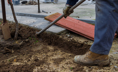 Worker digging a ditch with a hoe in a construction in a rural place. Man in boots and safety gloves. Many construction materials in the background.