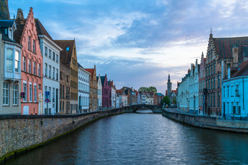 View of a canal and old historical buildings in Bruges, Belgium at dusk