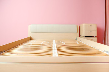 Photo of bed without mattress, chest of drawers