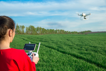 Female flying a drone at the field Wall mural