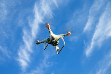 drone hovering in a bright blue sky. New technology in the aero photo shooting.