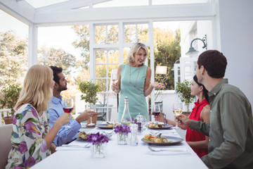 Group of friends interacting with each other while having meal together