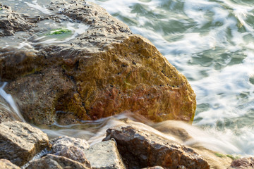 sea wave crashing on rock, long exposure photography for smooth water effect, old film look effect