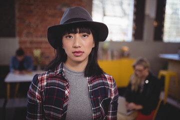 Portrait of confident young woman wearing hat at coffee shop