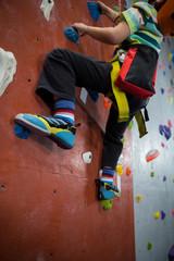 Boy practicing rock climbing in fitness studio