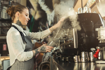 Fototapeta Tattooed barista making coffee in professional coffee machine obraz