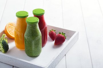 Fresh strawberry, orange and broccoli smoothie in bottles with fruits and vegetables on a white wooden rustic background