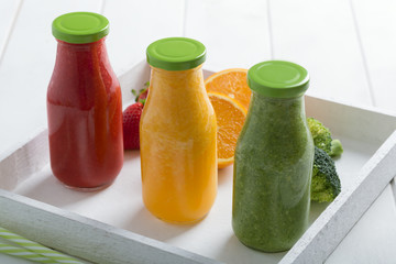 Fresh strawberry, orange and broccoli smoothie in three bottles with fruits and vegetables on a white wooden rustic background